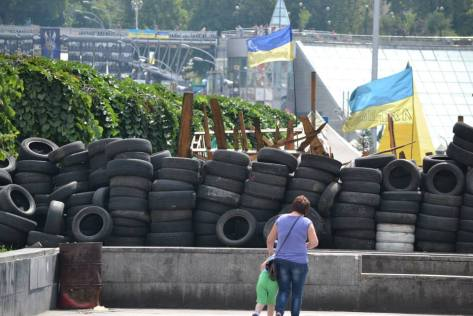 A mother shows her child stacked tire barricades, left over from the protestors' clashes with riot police on Kiev's Independence Square. Courtesy of Daniela Schmiedlechner