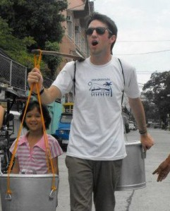 Conor Smith marches down the street carrying pails to fill with water, which is common in the Philippines.photo courtesy of Casey Conneely