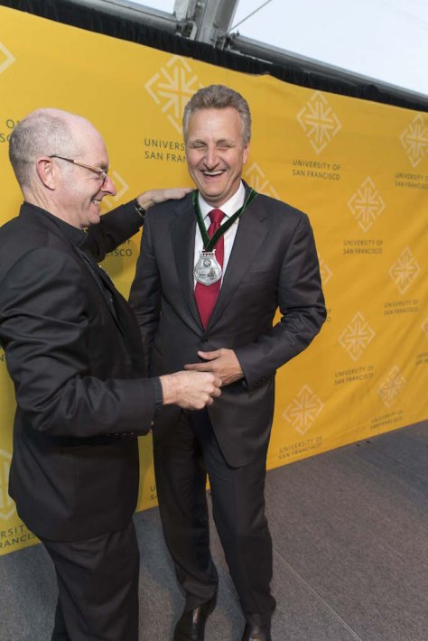 Father Fitzgerald presents Chronicle publisher Jeff Johnson with the California Prize for Service and the Common Good.